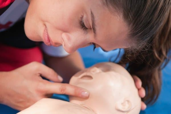 Woman practicing CPR on infant mannequin